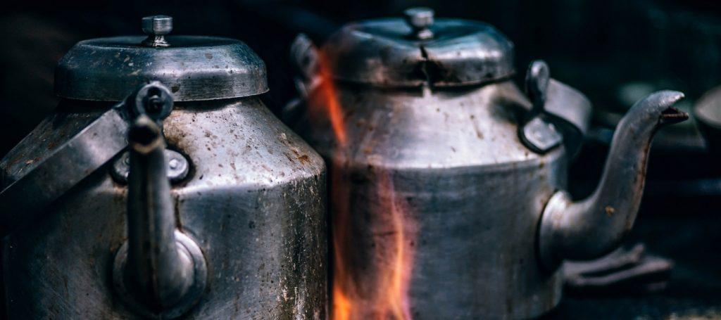 Geschiedenis Waterkoker: twee oude ketels op een houtkachel